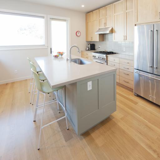 The center of this kitchen has a large island that has an eating bar and a built in sink. Light wood cabinets along the right side match the hardwood floors and set off the stunning stainless steel appliances.