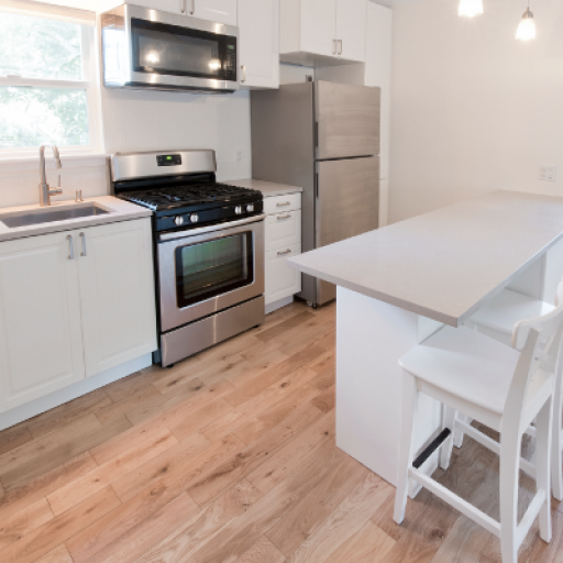 Looking into a bright white kitchen that has two stools pulled up to a white bar height counter in the middle and a wall with a sink and stainless steel appliances on the left. There are also two windows in the room with white shades.