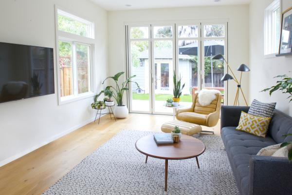 The open plan living room of the Berkeley bungalow is flooded with light from large windows and sliding glass doors