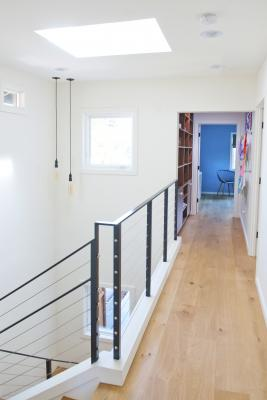 The modern stairway of the Berkeley bungalow leads to the open hallway on the second floor