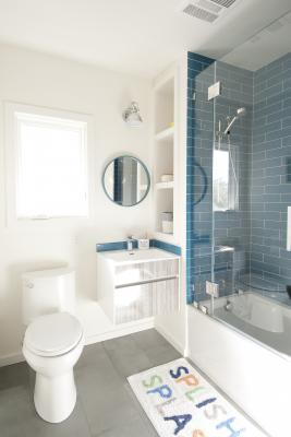 The Berkeley bungalow upstairs bathroom features a hanging vanity and a blue tiled bath and shower area