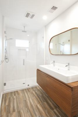 The Berkeley bungalow master bath is bright and warm with white tiles and fixtures warmed up with wood floors and vanity