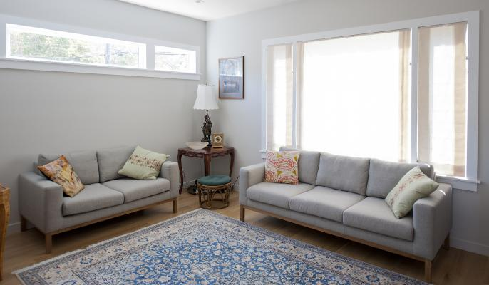 Another angle of the comfortable and modern living room with it's white walls and hardwood floors. There's a gray sofa set and a blue carpet. A row of window on the back wall and a giant window on the right bring in lots of natural light.