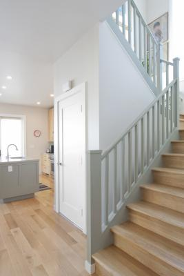 The kitchen is seen in the background of this photo featuring the transitional staircase.