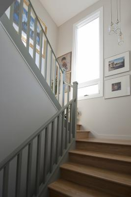 The bright stairway features the same gray trim and light wood floors creating a cohesive space. A large window and framed artwork on the walls completes the landing.