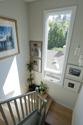 Another angle looking down the bright stairway which features the same gray trim and light wood floors creating a cohesive space. A large window and framed artwork on the walls completes the landing.