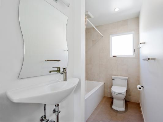 The full bath is compact and clean with a hanging sink, low-flow toilet, and neutral colors. The sink is on the left with the bathroom in the back corner. A window and the toilet are on the far wall.