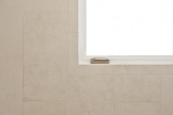 A close up of the tile wall and corner of the window. The tiles are light neutral colored and slightly mottled.