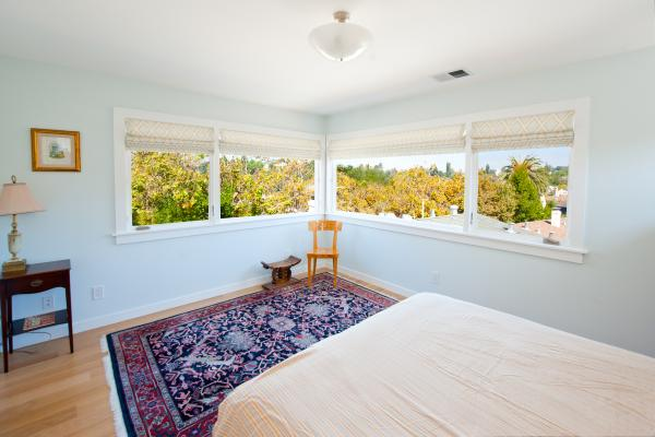 The windows on two walls meet in the corner to provide a stunning, continuous view in the master bedroom. The foot of the bed is in the foreground and a patterned carpet is on the floor. A wooden chair and stool are in the corner. The walls are light blue.