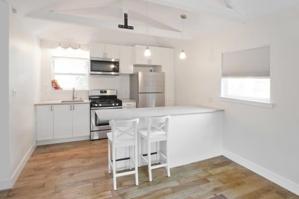 Looking into a bright white kitchen that has two stools pulled up to a white bar height counter in the foreground and a wall with a sink and stainless steel appliances in the back. There are also two windows in the room with white shades.