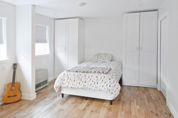 A white room with a Murphy bed in the down position flanked by two tall cupboards. Two windows are on the left side of the room and there's a guitar in a corner.