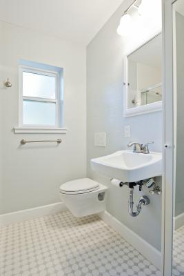 A white tiled bathroom showing a wall with a hanging toilet and sink. There's lighting and a mirror over the sink and a window on the far wall.