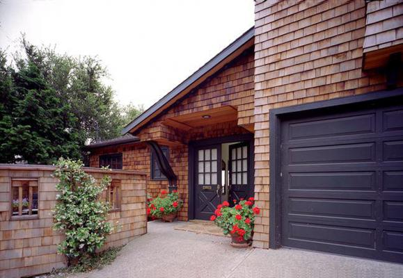 Front entryway with wood shingled sides and dark brown trim and matching garage. From Facade Renovation in Piedmont, California designed by Susan L. Wootan